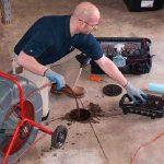 plombier déboucheur qui débouche une canalisation bouchée
