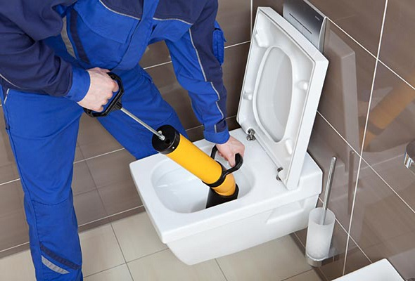 plombier déboucheur sui débouche une toilette avec une pompe à vide