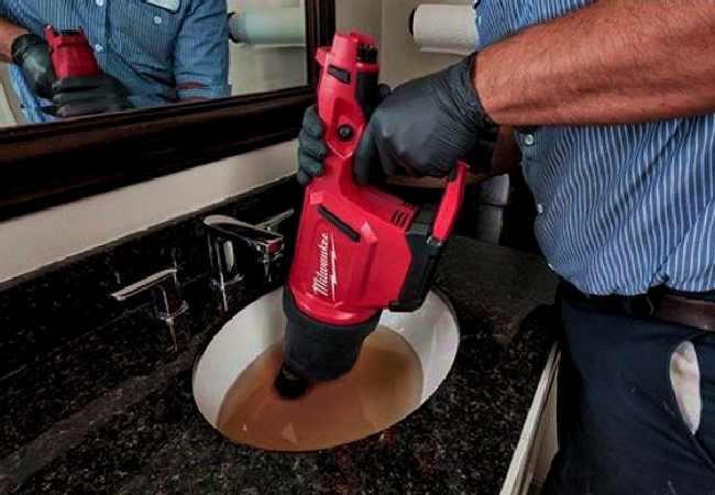 plombier déboucheur qui débouche un évier lavabo bouché