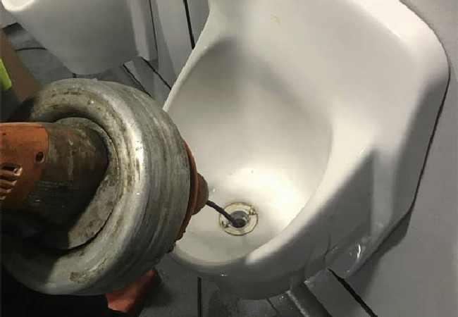 plombier déboucheur qui débouche un urinoir